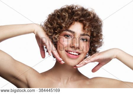 Smiling beautiful healthy freckled girl with curly hair