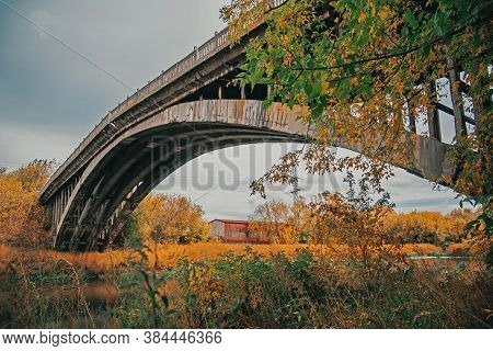 Abandoned Arched Bridge Among The Autumn Trees. Arched Cement Bridge Closed To Traffic Pictured Agai