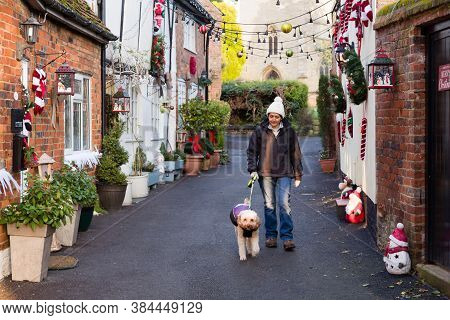 British Asian Indian Woman Walking Dog At Christmas In A Pretty Uk Street Scene With Old Cottages