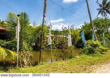 Colorful Buddhist Prayer Flags And Pond Among Green Tropical Nature In Wei Tuo Fa Gong Buddhist Temp