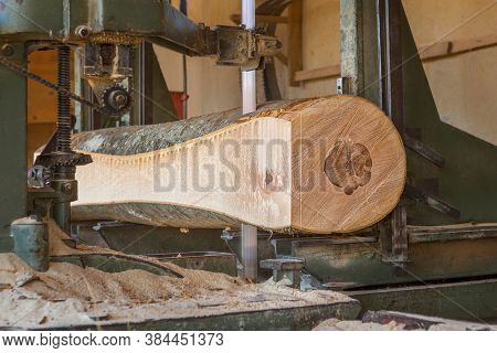 Sawmill cutting, wooden log being cut with chainsaw