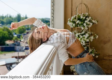 Attractive Sexy Woman Enjoying Her Comfortable Terrace. Young Woman Relaxing At Home, White Brassier