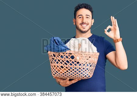 Young hispanic man holding laundry basket doing ok sign with fingers, smiling friendly gesturing excellent symbol