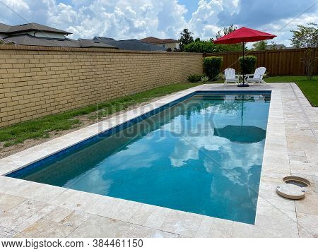 A Serene Backyard Setting With A Swimming Pool A Red Umbrella With A Blue Sky And White Clouds Refle