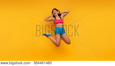 Sport Woman Jumps On A Yellow Background And Listen To Music. Happy And Joyful Expression.