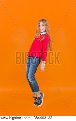Beauty, Look, Hairstyle. Girl In Red Sweater And Jeans Stand On Tiptoe. Kid Fashion And Style. Child