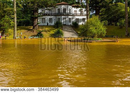 Furnas, Azores, Portugal - August 16, 2020: People swimming in a mineral thermal pool in the Terra Nostra botanical garden at Furnas, Sao Miguel island, Azores.