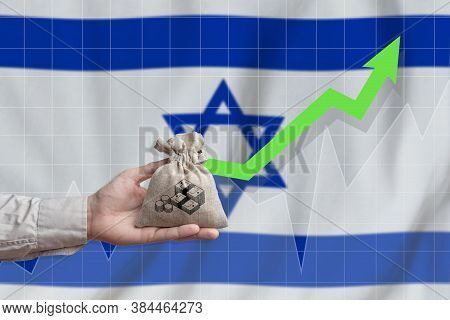 The Concept Of Economic Growth In State Of Israel. Hand Holds A Bag With Money And An Upward Arrow.