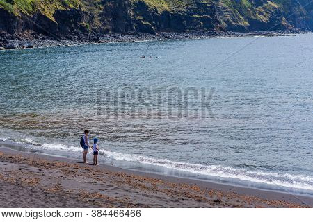 Mosteiros, Sao Miguel island, Azores, Portugal - August 15, 2020: People relaxing on a nice sandy beach of Mosteiros. Popular with both local people and tourists.