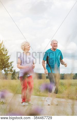 Fit and active senior couple running outdoors as exercise on path in summer