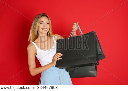 Happy Young Woman With Shopping Bags On Red Background. Black Friday Sale