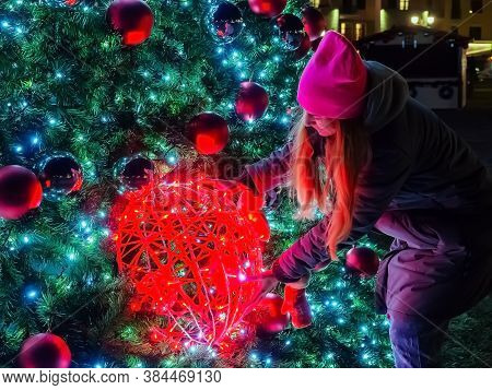 A Girl Holds On To A Giant Christmas Ball With Garlands Hanging On A Large Christmas Tree
