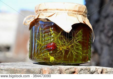 A Glass Jar With Juniper Jam Is On A Tree Stump.