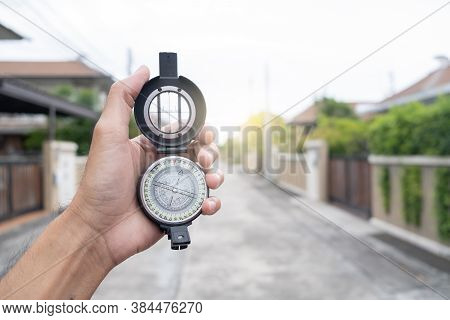 Man Holding Compass On Blurred Background. For Activity Lifestyle Outdoors Freedom Or Travel Tourism