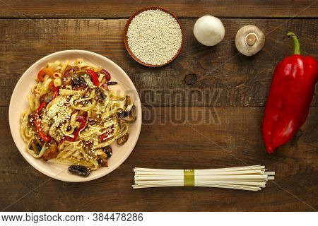 Udon With Chicken And Mushrooms In Pad Thai Sauce In A Beige Plate Next To Sesame And Udon.