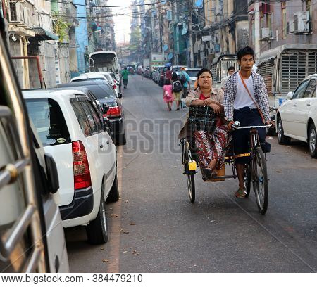 Yangon, Myanmar Feb 24, 2019: Myanmarese Passenger Sitting On The Bicycle Tricycle Taxi With The Dri