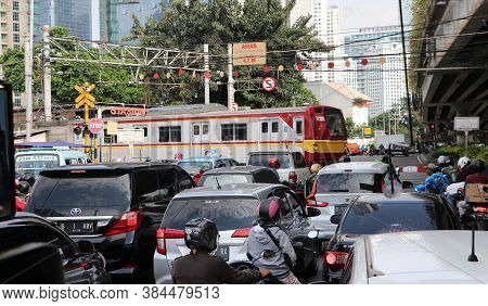 Jakarta, Indonesia May 6, 2019: The Train Runs Across The Road. Causing The Car To Stop To Wait Thus