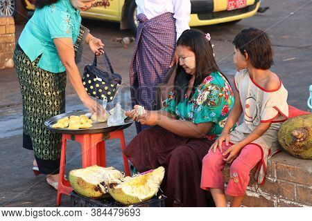 Yangon, Myanmar - Feb 25, 2019 : Myanmese Female Street Vendor And Daughter Sitting And Peeling Jack