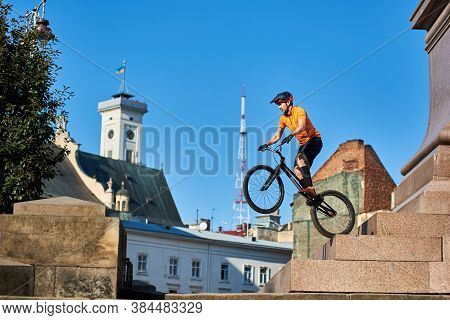 Horizontal Side Snapshot Of A Freestyle Trial Biker Performing Extreme Show On Monument Pedestal Dow