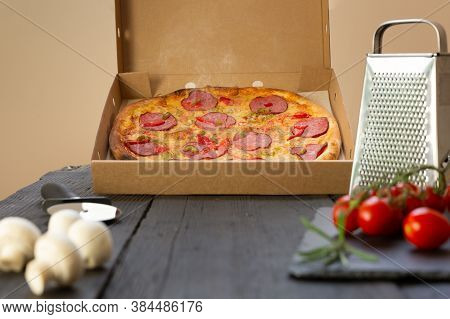 Hot Pizza And Ingredients On A Black Table