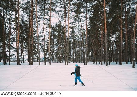 Active Adult Caucasian Woman Have Fun Are Skiing In Winter Snowy Forest. Active Healthy Lifestyle On