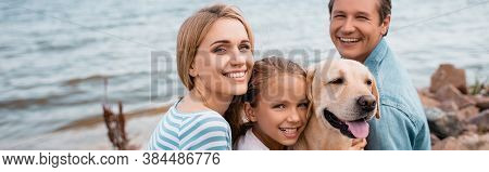 Panoramic Shot Of Parents And Daughter With Golden Retriever Looking At Camera On Beach