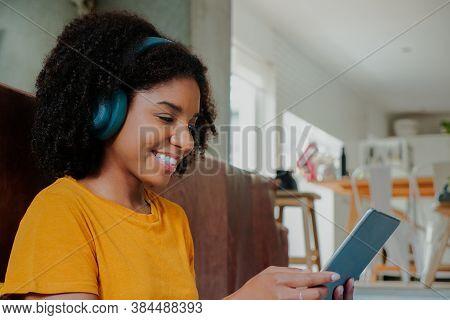 African American Teenage Female Wearing Headphones Listening To Music Scrolling On Digital Tablet Si