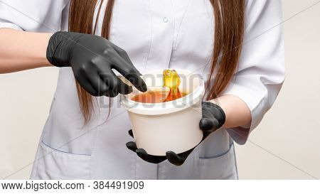 Honey Waxing. Natural Hair Removal. Female Beautician In White Medical Overall Black Latex Glove Hol