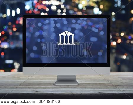 Bank Flat Icon On Desktop Modern Computer Monitor Screen On Wooden Table Over Blur Colorful Night Li