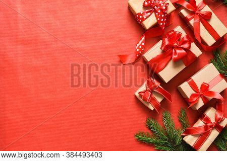 Beautiful Christmas Composition On A Red Background With Fir. Gift Boxes With Red Ribbons.