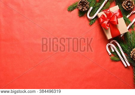 Gift Boxes With Red Ribbons And Candy Canes. Beautiful Christmas Composition On A Red Background Wit
