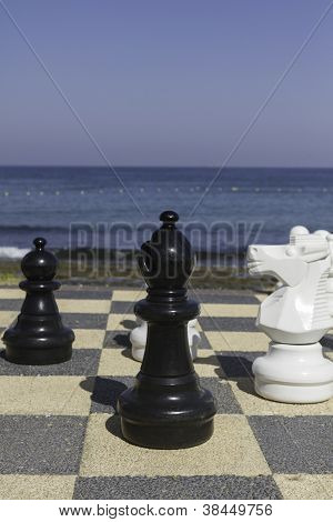 Large Chess Pieces On An Outdoor Board