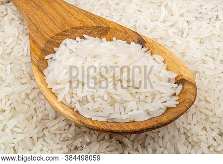 Pile Of Jasmin Rice In A Wooden Spoon On The Jusmin Rice Background.