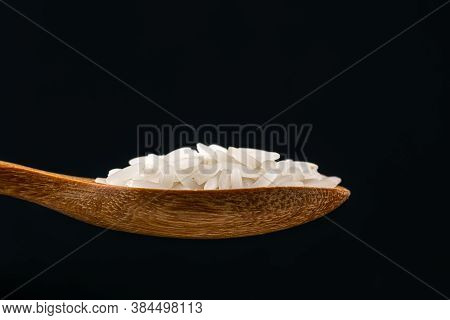Side View Of Jasmine Rice In A Wooden Spoon On Black Background.