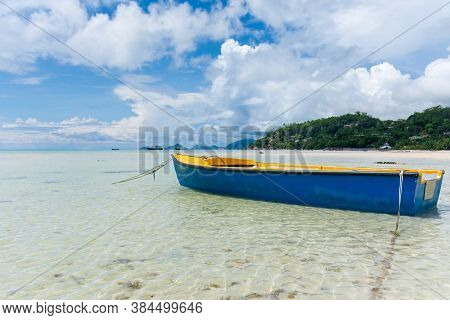 A Lone Boat Remains Moored In The Shallow Waters At Low Tide On The Island Of Mahe, Seychelles.