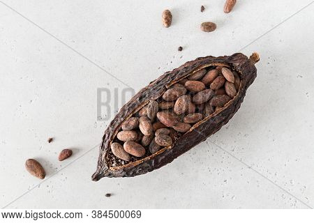 Cocoa Pod With Cocoa Beans On A White Concrete Background. Organic Food. Natural Chocolate. Top View