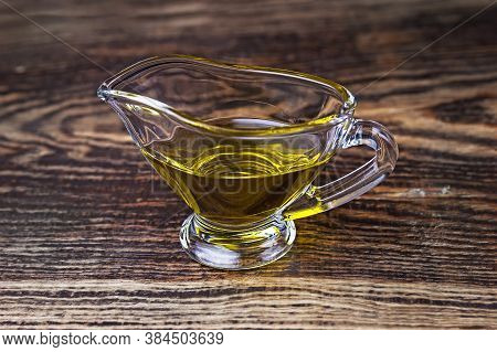 Olive Oil In A Glass Gravy Boat. Vegetable Oil On A Black Background.