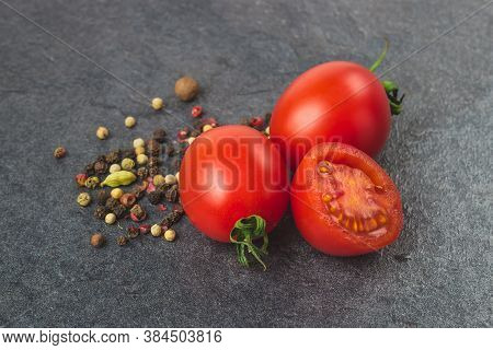 Cherry Tomatoes On A Black Background With Various . Seasoning And Tomato
