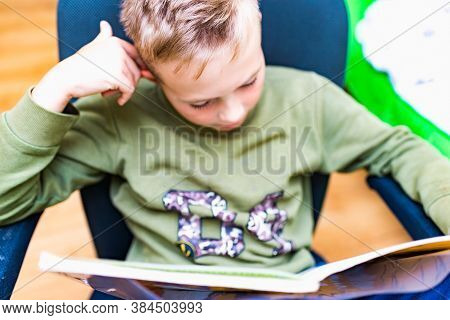 Top View Caucasian Nine Years Old Schoolboy Reading A Book, Learning Exercise Books For Homeschool W