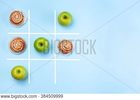 Healthy Vs Unhealthy Food, Green Apples Vs Cinnamon Buns In Tic Tac Toe Or Noughts And Crosses Game,