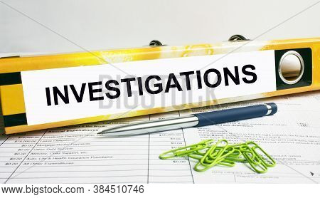 Text Investigations On The Folder That Is Located On The Financial Reports With Blue Pen And Green P
