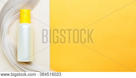 Shampoo Bottle Mockup Strand On Lock Curl Of Blonde Hair On Orange Color Background. Yellow Bottle S