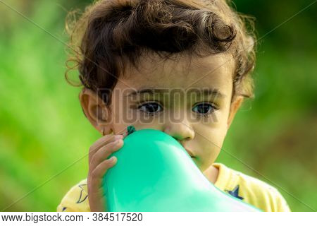 A Small Child Holding A Blue Balloon Thinking About His Problem, Portrait Little Boy Outdoor, Child