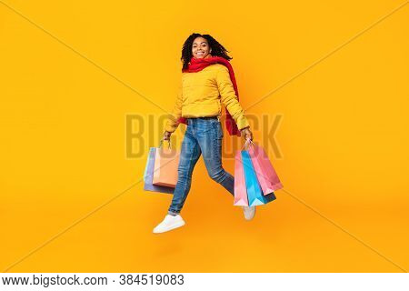 Winter Shopping And Sales. African Girl With Shopping Bags Jumping In Mid-air Posing Wearing Warm Cl