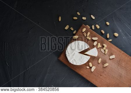 Cheese Camembert With Mold And Nuts On Wooden Board