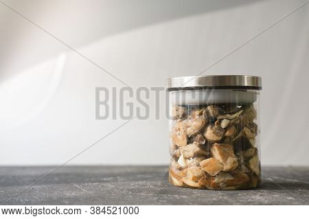 Homemade Canned Pickled Forest Mushrooms On A Grey Table. Glass Jar With Mushrooms Conserved For Win
