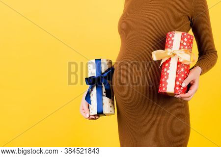 Close Up Of Two Gift Boxes In Pregnant Womans Hands Against Her Belly At Yellow Background. Is It A