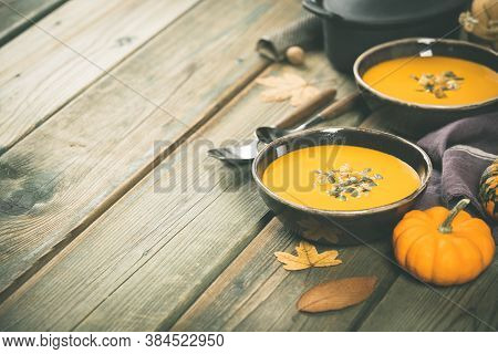 Pumpkin Soup On Wooden Table, Space For Text