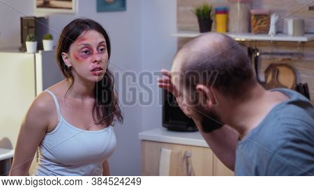 Traumatised Woman Yelling At Drunk Man Holding A Bottle Of Wine. Abused Terrified Beaten Wife Covere