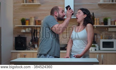 Angry Man Yelling At Unfaithful Wife In The Kitchen. Jealous Partner Cheated Frustrated Offended Irr
